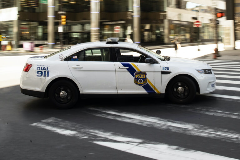 A police car drives in Philadelphia, Tuesday, March 24, 2020. (AP Photo/Matt Rourke)