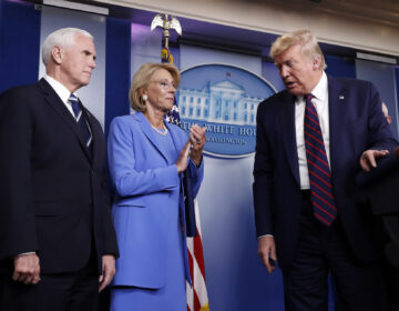 President Donald Trump leaves the podium after a briefing in the James Brady Press Briefing Room, Friday, March 27, 2020, in Washington, as Vice President Mike Pence and Education Secretary Betsy DeVos watch, (AP Photo/Alex Brandon)