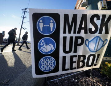 Pedestrians walk past a sign on in Mount Lebanon, Pa.,reminding people to wear a mask, wash their hands and practice social distancing, Wednesday, Nov. 18, 2020. (AP Photo/Gene J. Puskar)