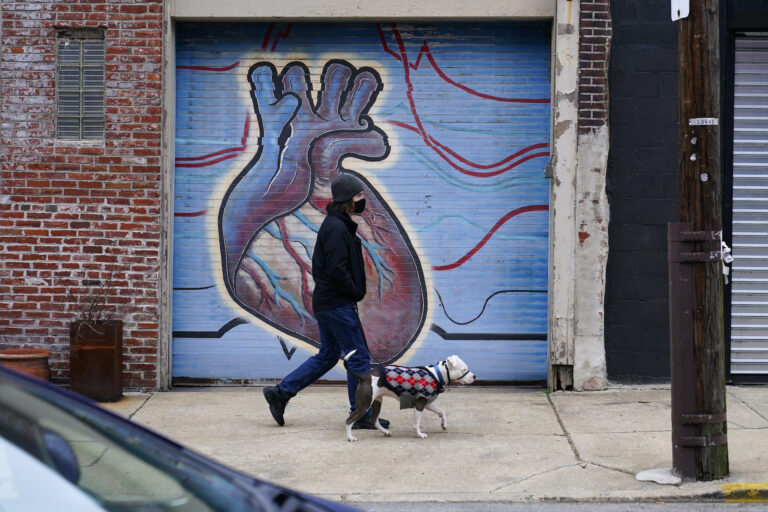 A man wearing a face mask to protect against the spread of the coronavirus walks with a dog, Wednesday, Dec. 9, 2020, in Northeast Philadelphia. (AP Photo/Matt Slocum)