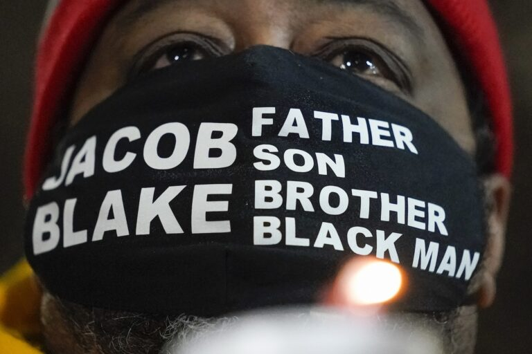 Jacob Blake Sr., father of Jacob Blake, holds a candle at a rally Monday, Jan. 4, 2021, in Kenosha, Wis. (AP Photo/Morry Gash)