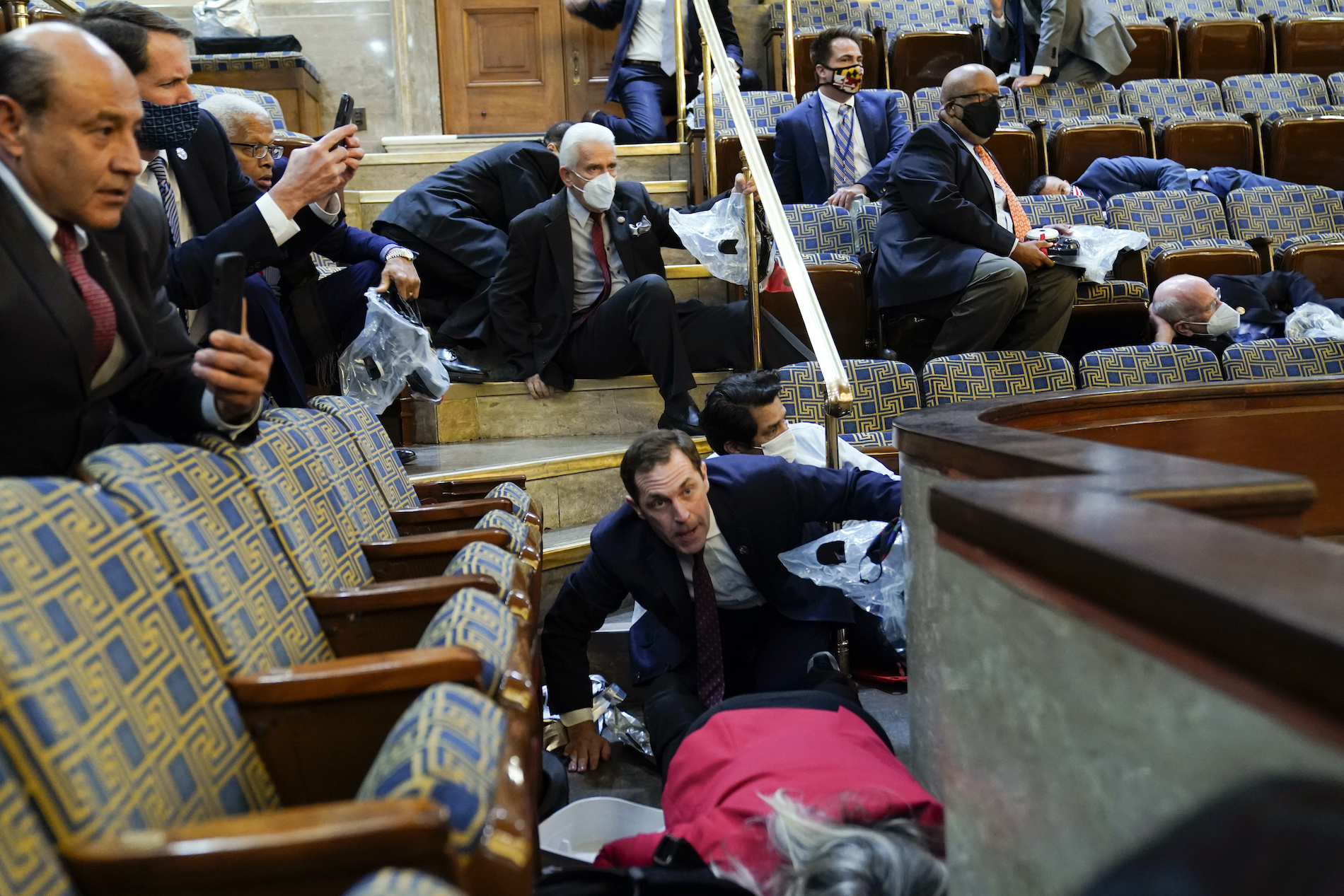 People shelter in the House gallery as pro-Trump insurrectionists try to break into the House Chamber at the U.S. Capitol