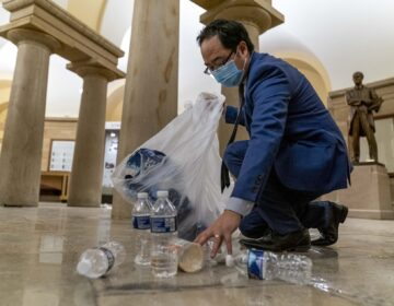 Rep. Andy Kim, D-N.J., cleans up debris and trash strewn across the floor in the early morning hours after protesters stormed the Capitol in Washington, Thursday, Jan. 7, 2021. (AP Photo/Andrew Harnik)