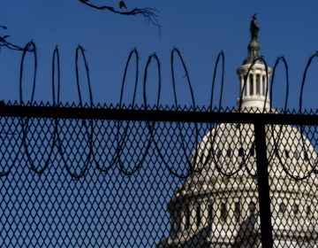 The Dome of the Capitol Building is visible through razor wire installed on top of fencing on Capitol Hill in Washington, Thursday, Jan. 14, 2021. (AP Photo/Andrew Harnik)