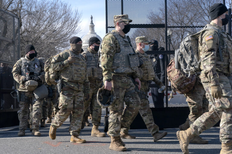 With the U.S. Capitol in the background, members of the National Guard change shifts as they exit through anti-scaling security fencing