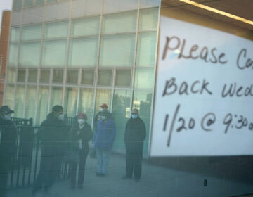 People waiting in line are reflected in the glass windows of a vaccination site in Paterson, N.J., Tuesday, Jan. 19, 2021. A sign on the door of the vaccination site, which takes walk-ins rather than appointments, said it would be open tomorrow. (AP Photo/Seth Wenig)