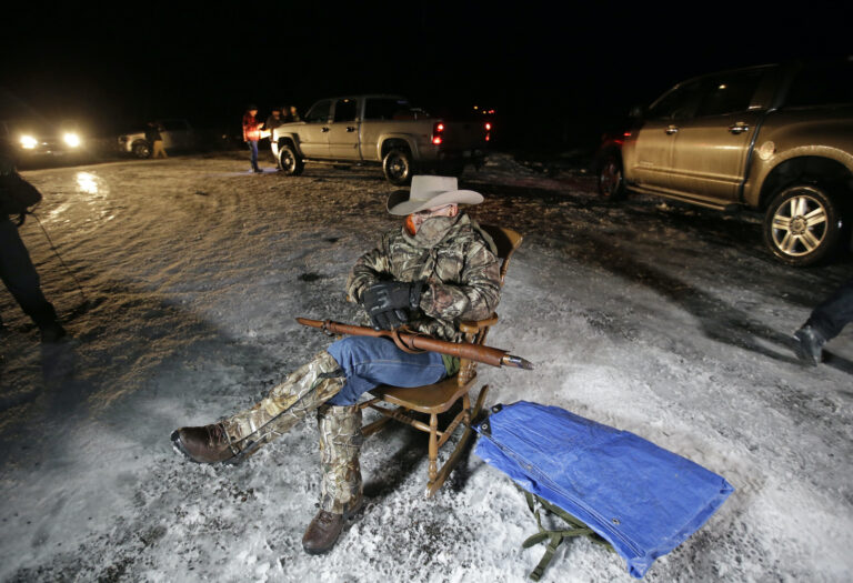 In this Jan. 5, 2016 file photo Arizona rancher LaVoy Finicum holds a gun as he guards the Malheur National Wildlife Refuge near Burns, Ore. (AP Photo/Rick Bowmer)
