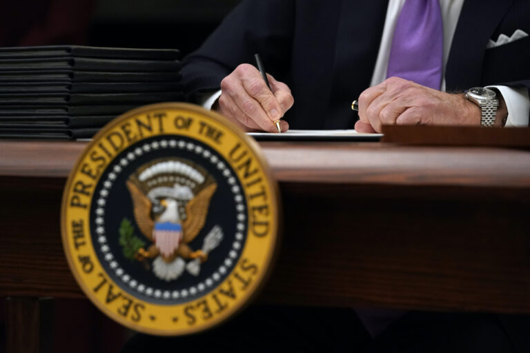 President Joe Biden signs executive orders after speaking about the coronavirus in the State Dinning Room of the White House, Thursday, Jan. 21, 2021, in Washington. (AP Photo/Alex Brandon)