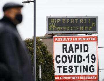 A person wearing a face mask as a precaution against the coronavirus stands near a sign advertising a rapid COVID-19 testing site in Philadelphia, Monday, Jan. 25, 2021. (AP Photo/Matt Rourke)