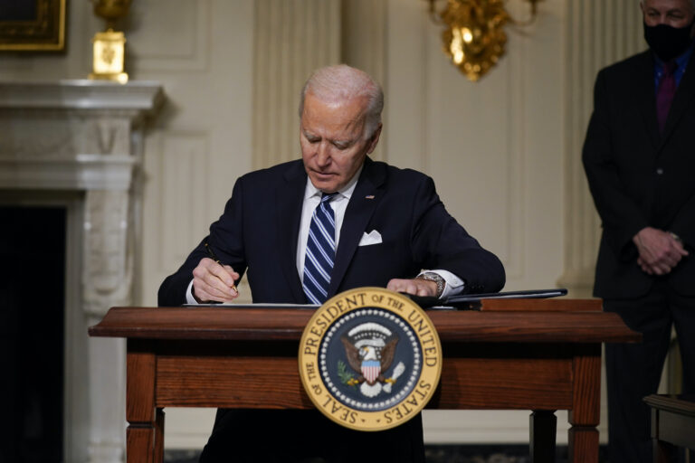 President Joe Biden signs an executive order in the State Dining Room of the White House. (AP Photo/Evan Vucci)