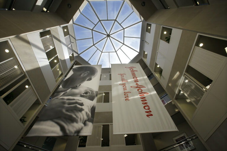 In this July 30, 2013, file photo, large banners hang in an atrium at the headquarters of Johnson & Johnson in New Brunswick, N.J. (AP Photo/Mel Evans)