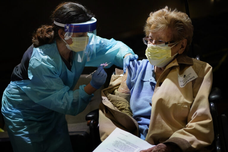 Helen Fitzpatrick, 97, right, receives a COVID-19 vaccine administered by Dr. Hillary Cohen at Englewood Health