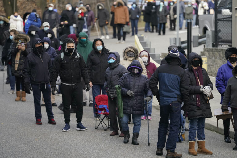 People wait in line for the COVID-19 vaccine in Paterson, N.J.