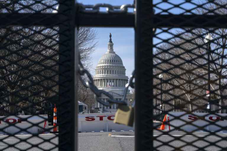 With the U.S. Capitol in the background, a lock on anti-scaling security fencing is seen