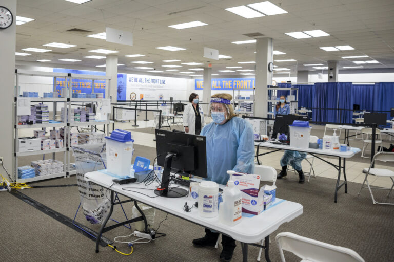 Health care workers prepare to give COVID-19 vaccinations at a former Sears store turned in to a vaccination site, in Rockaway, N.J.