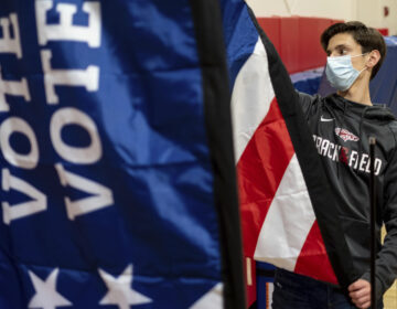 Thomas Hedrich sets up voting flags at a polling location.