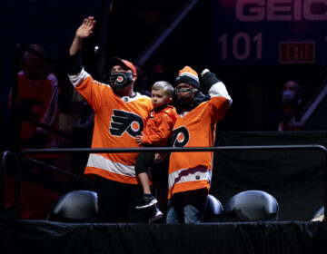 Josh and Amanda Hatheway, accompanied by their young son, wave from their seats at the Wells Fargo Center.