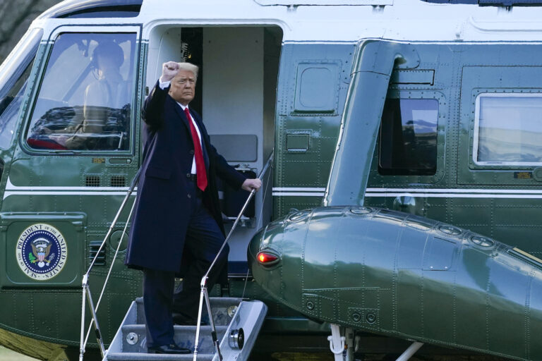 President Donald Trump gestures as he boards Marine One on the South Lawn of the White House