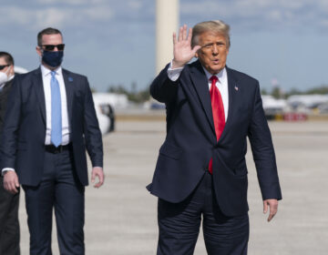 Former President Donald Trump waves to the members of the media