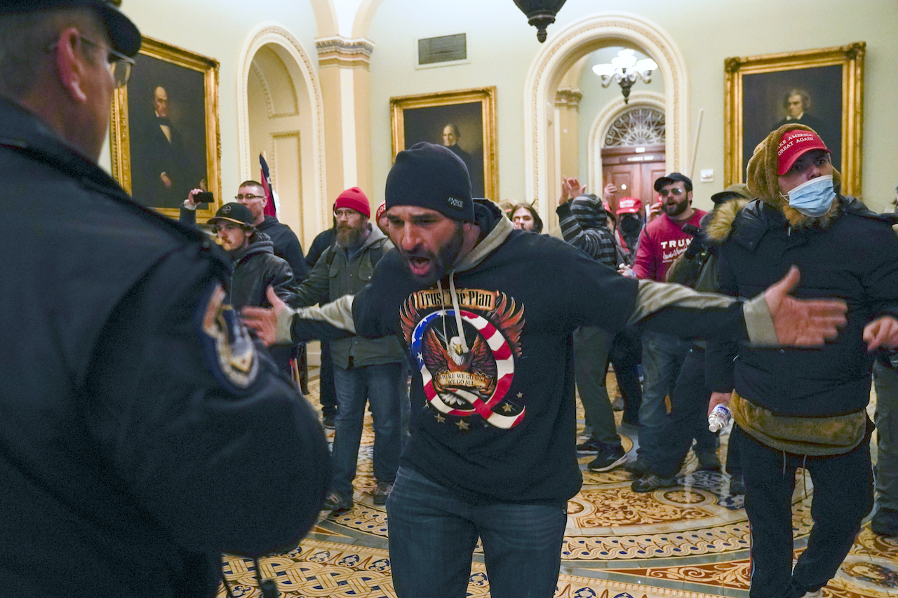 Pro-Trump insurrectionists gesture to U.S. Capitol Police in the hallway outside of the Senate chamber at the Capitol