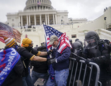 Pro-Trump rioters try to break through a police barrier at the Capitol
