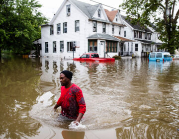 In this June 20, 2019 file photo, Chris Smith makes his way through floodwaters in Westville after severe storms swept across southern New Jersey. (AP Photo/Matt Rourke)