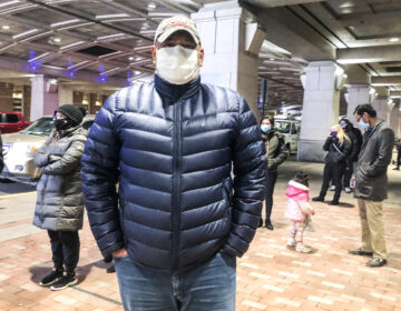 Julio Polanco, a behavioral care specialist at Children's Crisis Treatment Center, stands in line at Philadelphia's community vaccination clinic at the Pennsylvania Convention Center. (Nina Feldman/WHYY)