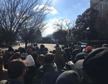 A crowd of about 50 presses towards the security barrier in an unsuccessful attempt to hear parts of the inauguration program. (Mark Eichmann/WHYY News)