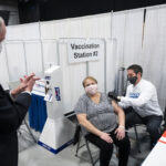 Phil Murphy, New Jersey's governor, left, applauds after a person receives a dose of a Covid-19 vaccination at the New Jersey Convention and Exposition Center in Edison, New Jersey, U.S., on Friday, Jan. 15, 2021. New Jersey will expand Covid-19 vaccinations to people 65 years old and over and those ages 16 to 64 who have