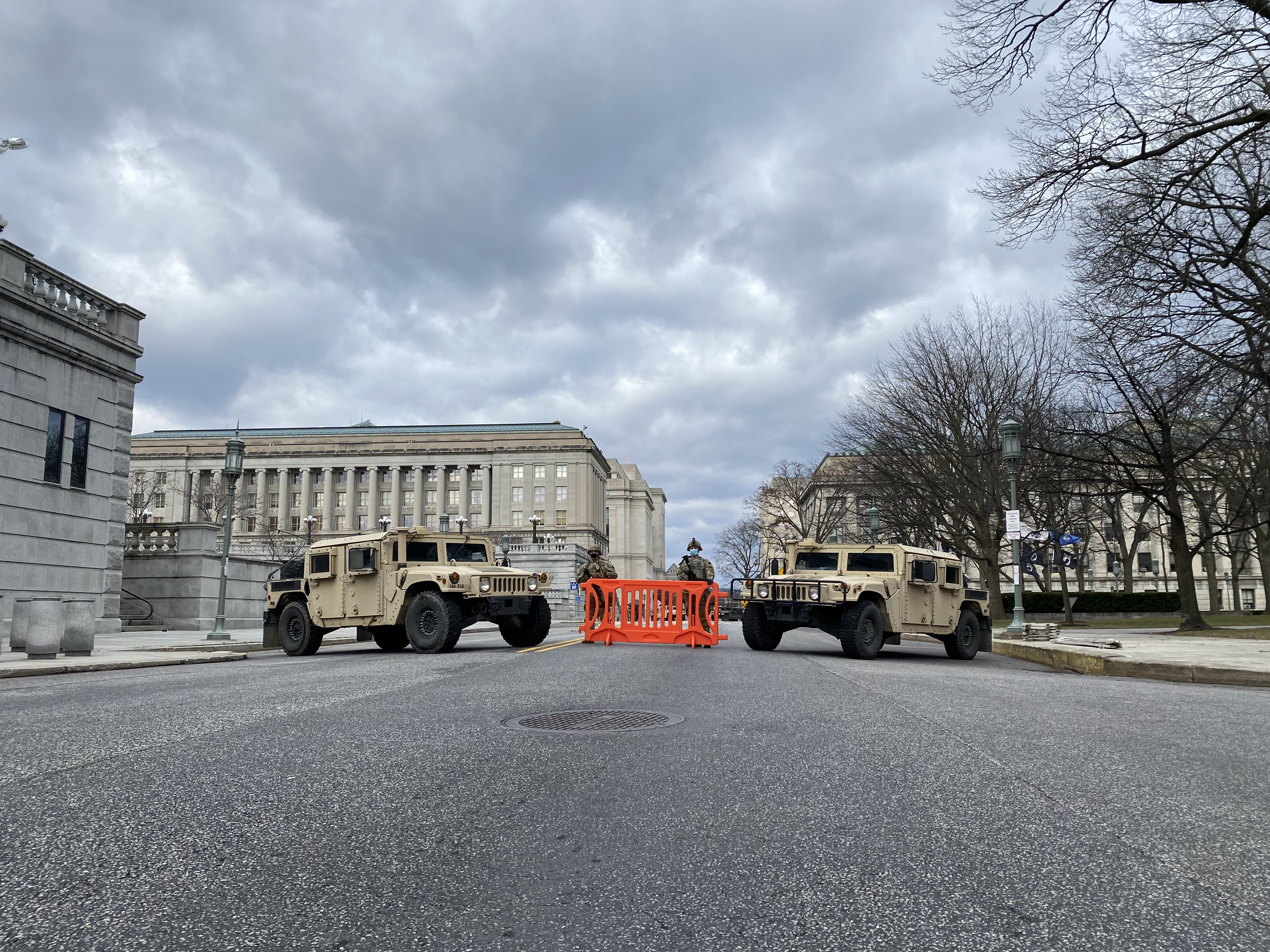 Two armored humvees are parked on a street near the Pa. state Capitol
