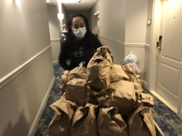 Cassie Brown pushes a cart filled with catered meals down a hallway. Each bag contains enough food for a day. (Cris Barrish/WHYY)