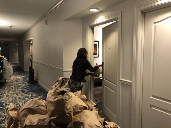 At lunchtime, Cassie Brown delivers a package of three meals to feed a guest for 24 hours. (Cris Barrish/WHYY)