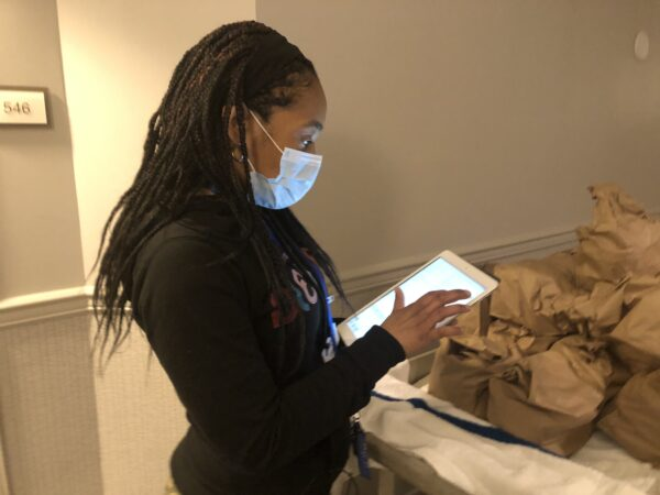Cassie Brown documents meal deliveries and wellness checks on her tablet. (Cris Barrish/WHYY)
