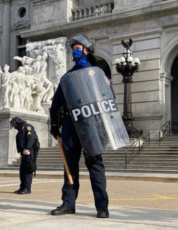 A police officer with a shield stands guard outside the Pa. Capitol
