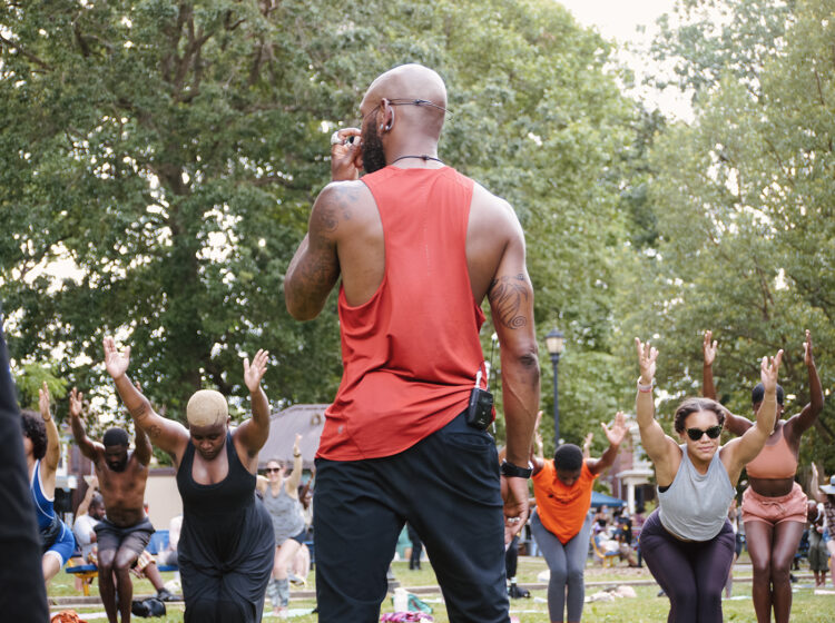A Black yoga instructor from Spirits Up! leads an exercise class outside for people of color