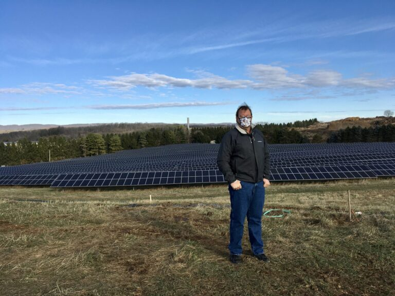 Cory Miller, executive director of the University Area Joint Authority, in the State College area of Centre County, standing in front of a UAJA solar panel project. (Anne Danahy / StateImpact Pennsylvania)