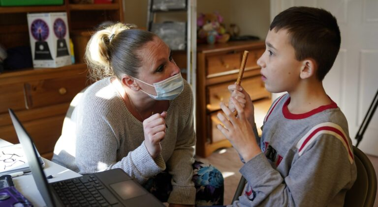 Paraprofessional Jessica Wein helps Josh Nazzaro, who lives with autism, with his classwork while attending class virtually from his home