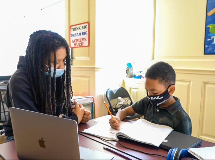 A young black girl and boy studying and doing homework with masks on