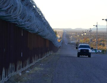 A U.S. Border Patrol vehicle drives along the border fence