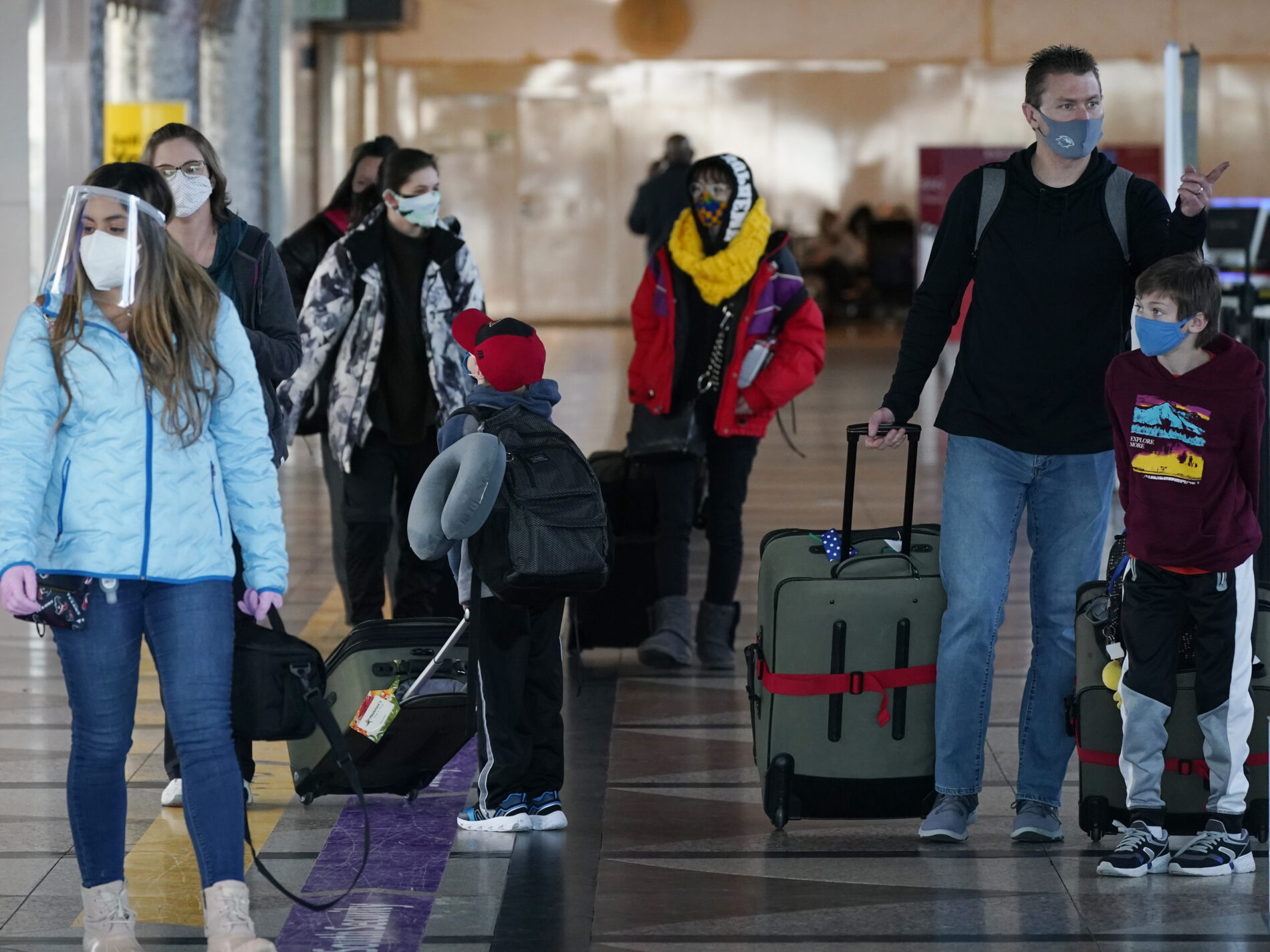 Travelers wear face masks in the main terminal of Denver International Airport