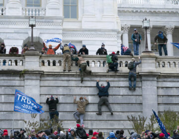 Pro-Trump insurrectionists climb the west wall of the the U.S. Capitol