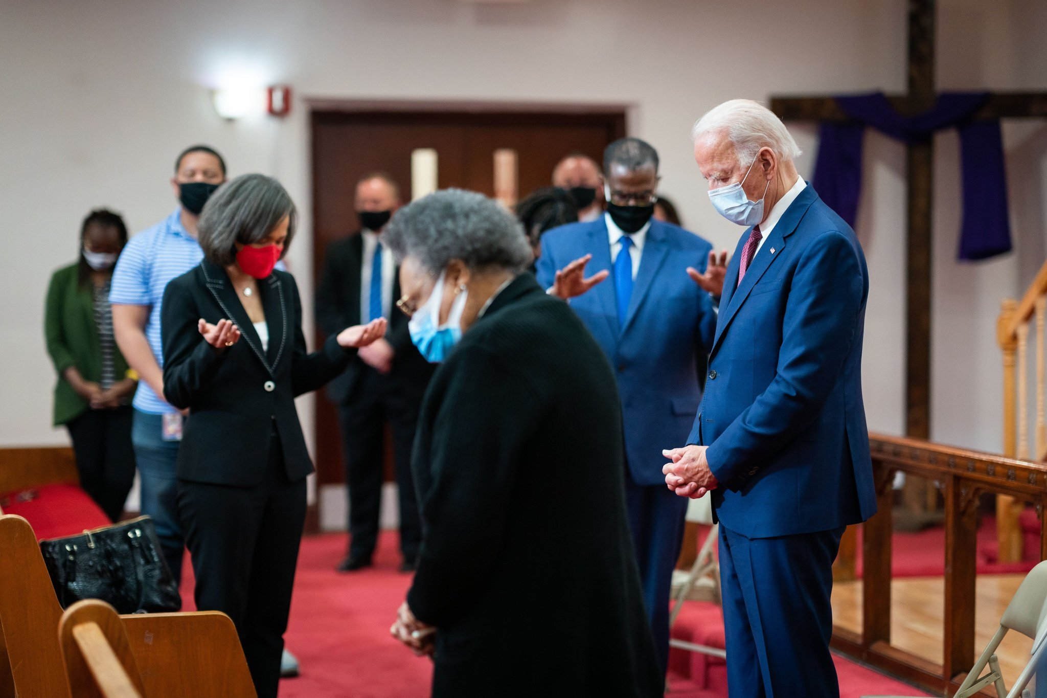 Rev. Silvester Beaman, Joe Biden and others stand inside a church with their heads down in prayer