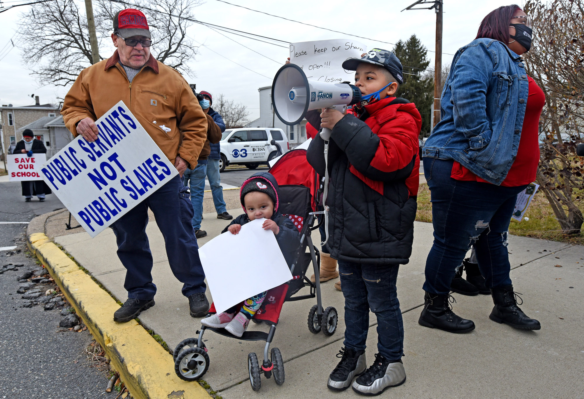 Activist Eulisis Delgado, left, protests school closures with children and their parents in front of Harry C. Sharp Elementary School