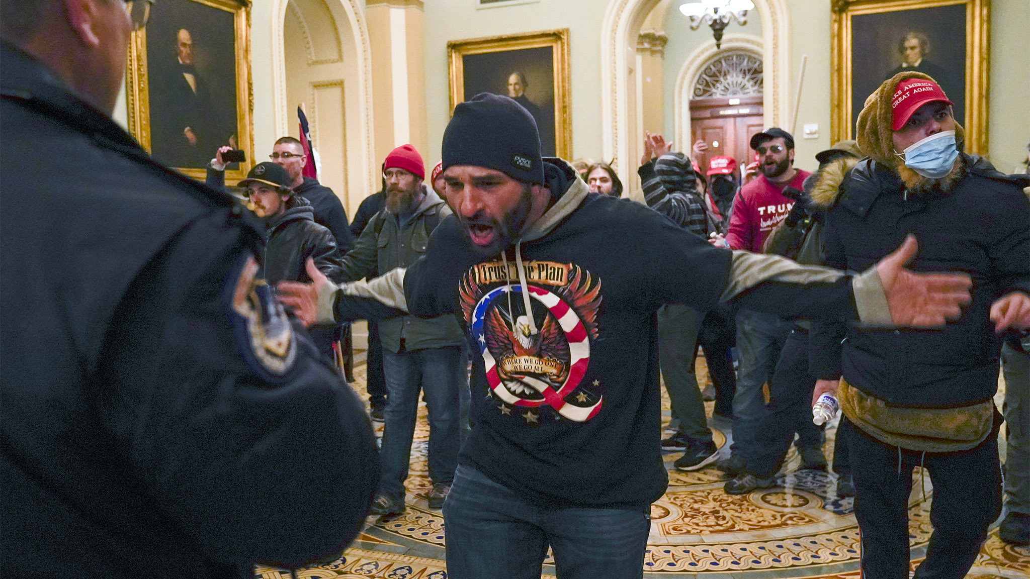 A pro-Trump insurrectionist gestures to U.S. Capitol Police in the hallway outside of the Senate chamber
