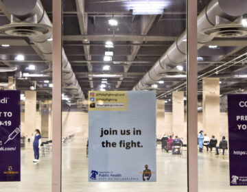Signs on the window of the city's first mass vaccination at the Pa. Convention Center on its opening day, Jan. 8. (Kimberly Paynter/WHYY)