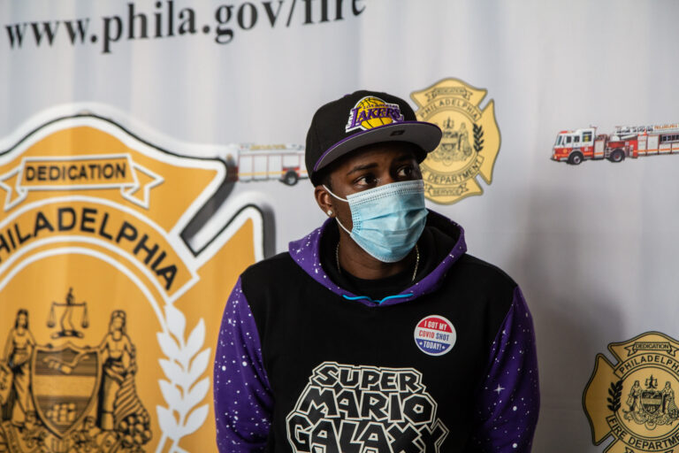 Eric Crawford sits in front of a Philadelphia Fire Department banner while wearing a mask