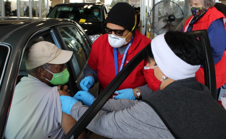 A Delaware resident is vaccinated against COVID-19 at a drive-thru site