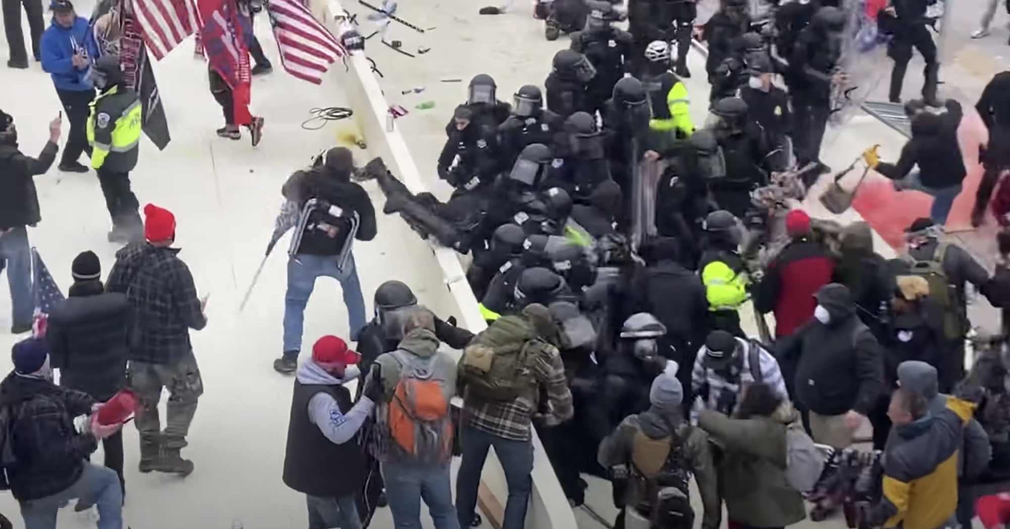 A screenshot of a YouTube video that reportedly captures Sanford, bottom left, as he hurls an object at Capitol Police.