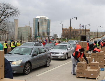 Volunteers distribute boxes of food to a long line of drivers