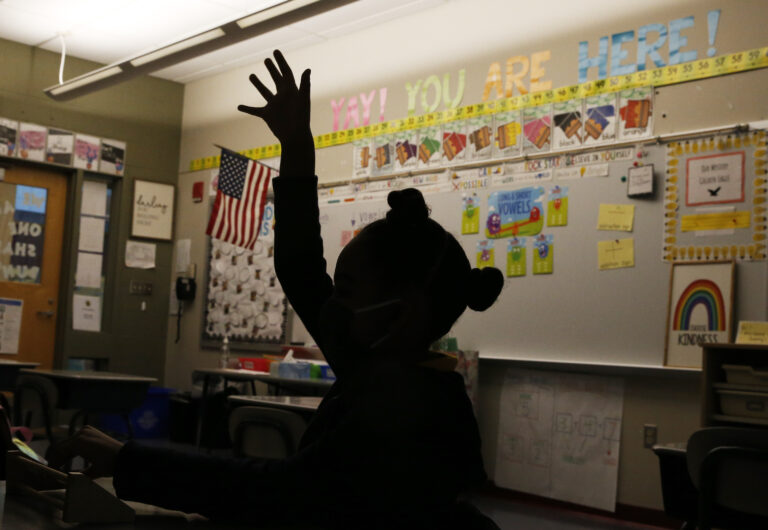 A first grade student raises her hand